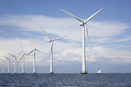 Large white windmills in the sea with a sailboat