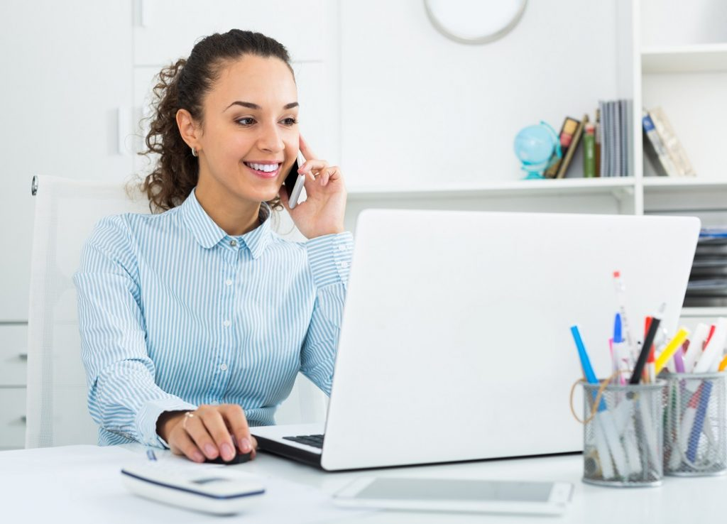 Positive,Businesswoman,Talking,On,Mobile,Phone,In,Modern,Office